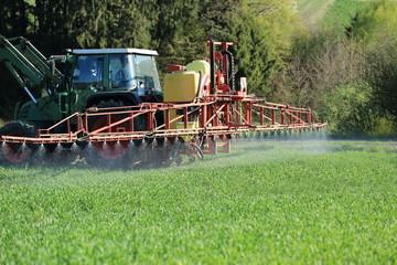Traktor beim Spritzen von Pestiziden
