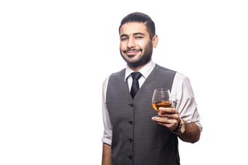 Handsome bearded businessman holding a glass of whiskey. smiling and looking at camera. studio shot, isolated on white background.