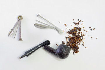 Smoking set: tamper, cleaner (multitool), wooden pipe with metal filter (cooler) and scattered tobacco