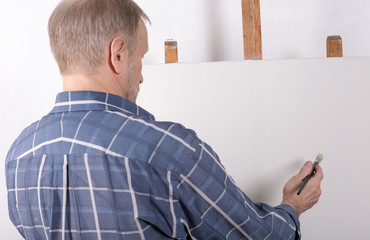 An artist in studio thinking in front of white canvas