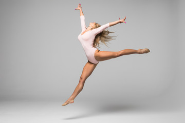 young modern gymnast dancer jumping on white background Wall mural