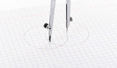 Drawing circle  compass on squared sheet paper.