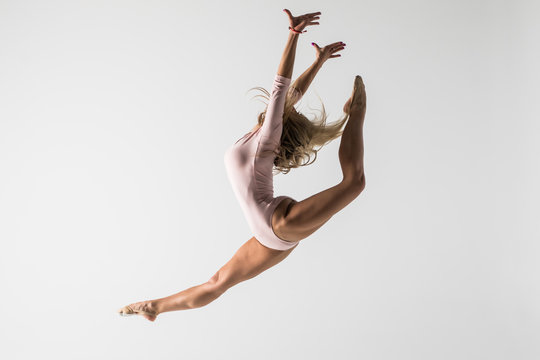 young modern gymnastics woman jumping on white background