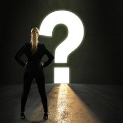 Geschäftsfrau steht vor einem leuchtenden Fragezeichen-Durchgang