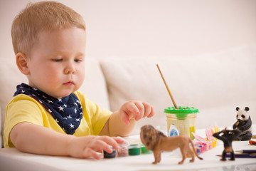 Cute little toddler boy in yellow shirt sitting at table and drawing with colorful paints. indoors. child having fun. Early learning. Creative. Toddler drawing.