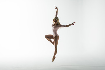 Studio shot of young athletic woman doing modern dance moves