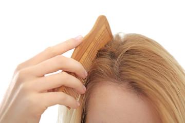 Young woman brushing hair, closeup