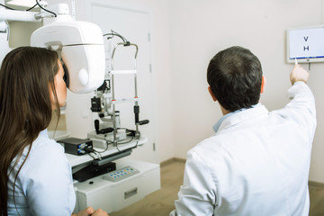 patient woman having her eyes examined by an optometrist using phoropter, in ophthalmology clinic.