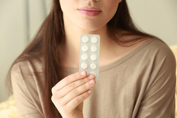 Beautiful young woman with pills at home, closeup