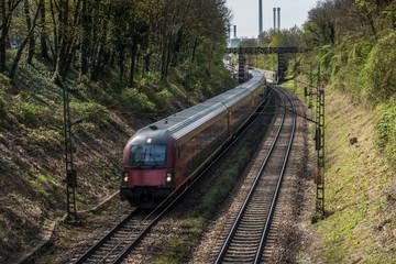Zugverkehr in München mit Heizkraftwerk Süd im Hintergrund