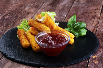 Breaded mozzarella cheese sticks with tomato ketchup and bbq sauce