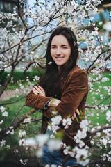 Long haired young girl near a blossom apricot tree.