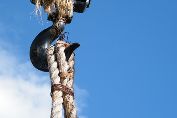 Black Hook Holding Old Rope with Blue Sky and White Clouds