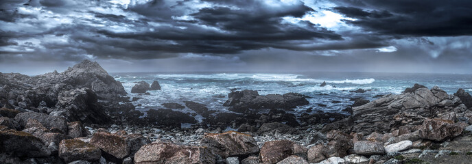 Foto op Aluminium Kust Foggy view of Pebble Beach California coast with storm clouds and rough seas causing waves to crash on rocks. The beach is shaped by erosion and climate change.