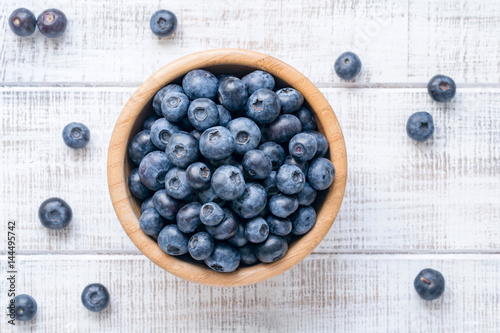 Bowl of fresh blueberries on vintage white background  Top