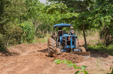 A tractor working in farm with  agricultural workers .