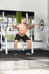Fitness Man Using Barbell Exercising Legs Inside Gym