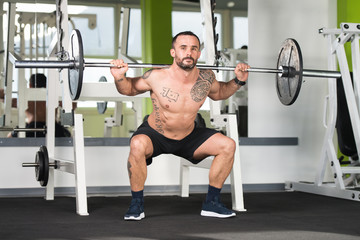 Athlete Doing Exercise For Legs With Barbell