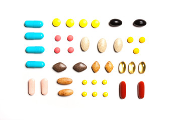 Vitamins, dietary supplements in a row , Background from multi-colored tablets
