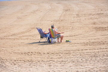 An elderly couple is resting on the Mediterranean coast in Spain