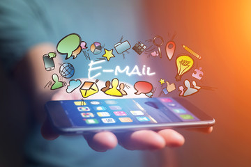 Concept of man holding smartphone with email title and multimedia icons flying around