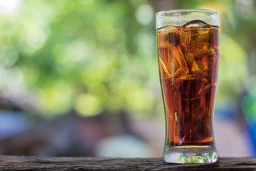 Glass of cola in bokeh background
