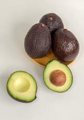 Brown avocado isolated with green half with seed white background