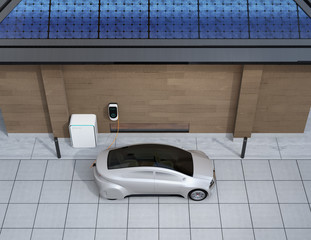 Silver car charging in home EV charging station. Power supply by roof mounted solar panels. 3D rendering image.