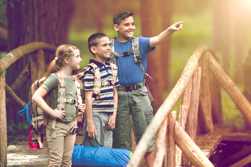 kids scouts traveler with backpack hiking on bridge