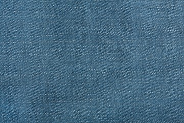 Denim jeans texture background with torn. The texture of the colored cotton fabric. Stitched texture jeans background. Fashion jeans button. Pocket and rivet on jeans. Fiber and fabric structure.