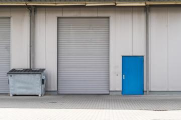 Silbernes Rolltor mit Container und blauer Tür