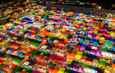 Night light aerial view multiple colours roof top weekend market, cityscape background