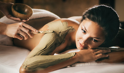 The girl enjoys mud body mask in a spa salon. Focus on the hand with the stick. Luxury treatment. Fototapete