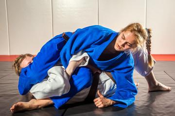 Judo, Jiu Jitsu. Two women are fighting on tatami. Blue and white kimano. Painful reception. Ground floor