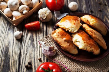 Hearty and tasty food, national Ukrainian cuisine, pies made of yeast dough with mushrooms, tomatoes and spices on rushnyk on a dark rustic wooden background