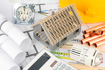 house building concept model on architect plans with calculator heating thermostat copper pipes construction concept background
