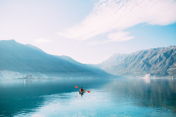 Kayaks in the lake. Tourists kayaking on the Bay of Kotor, near the town of Perast in Montenegro. Aerial Photo drone.