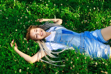 Beautiful young girl lying with a smile on the clover field. Girl Enjoying Nature. Spring Meadow. Grass and Flowers