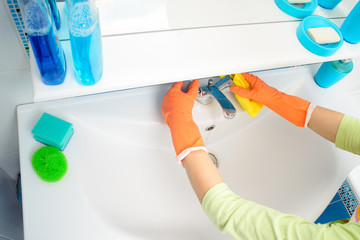 Cleaning - cleaning bathroom sink and faucet with detergent in rubber gloves with sponge - housework, spring cleaning concept