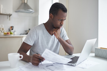 Young serious african american man sitting at kitchen table in front of open laptop, concentrated on paperwork, paying domestic bills using online banking application, planning household budget