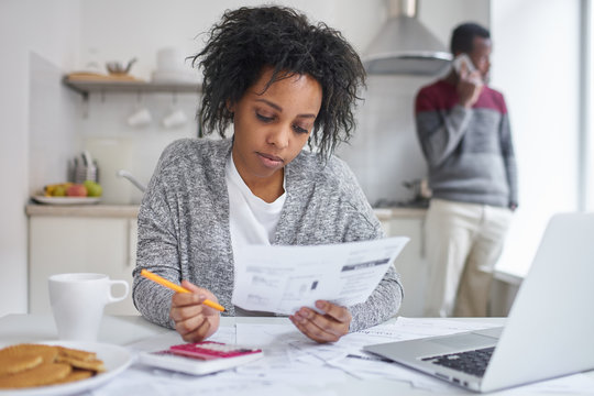 African american female reading piece of paper, calculating gas and electricity bills, sitting at kitchen table with laptop, calculator and documents, managing family finances, husband on background