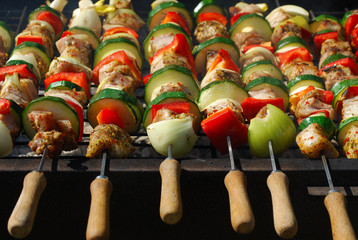 Summer time outdoor oil drum barbecue with shish skewers of chicken and vegetables in the garden