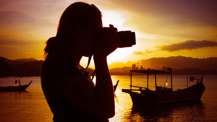 Girl taking a photo with a DSLR digital camera of the beach during sunset in tropical Langkawi island, Malaysia