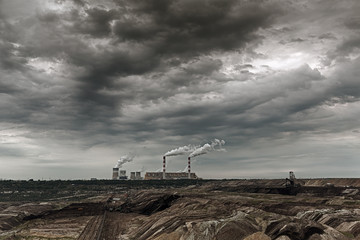 Storm clouds over open pit mine and power plant.