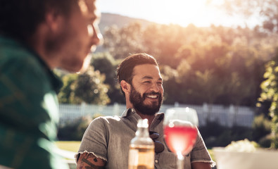 Young man sitting outdoors with friends smiling