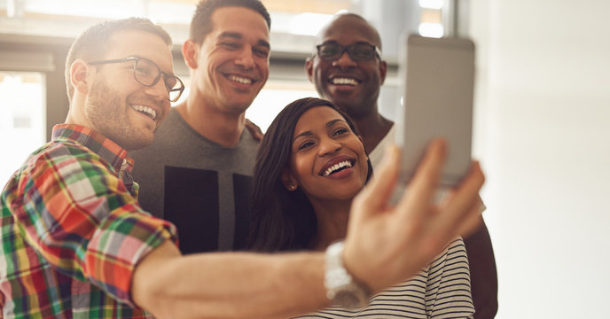 Cheerful office workers taking selfie with smartphone