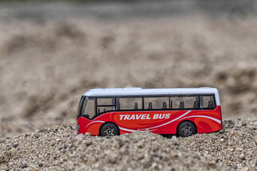 Travel bus, toy for kids in the sand. Shallow depth of field.