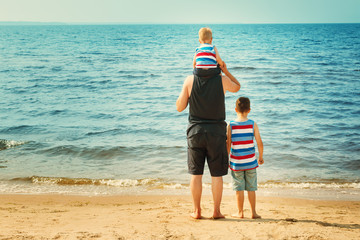 Wall Mural - Father and sons walking at the beach at sea