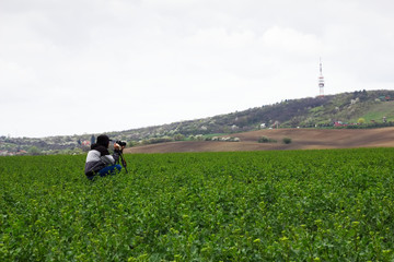 Photographer with a tripod photographing landscapes. Man takes a picture in the middle of field.
