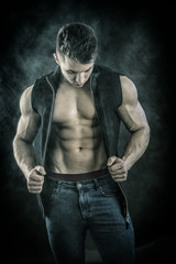 Handsome young muscular man shirtless wearing jeans and vest on naked chest, on dark background in studio shot